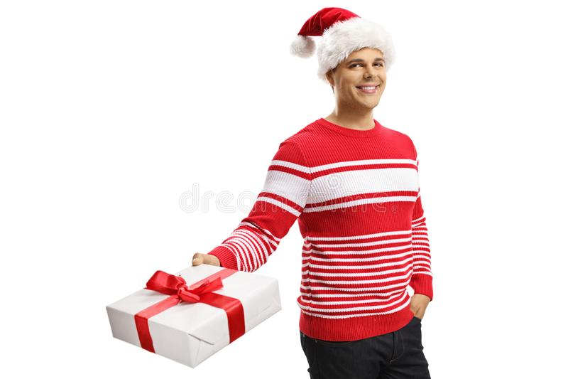 Homem novo alegre que veste um chapéu de Papai Noel e que guarda um presente imagem de stock