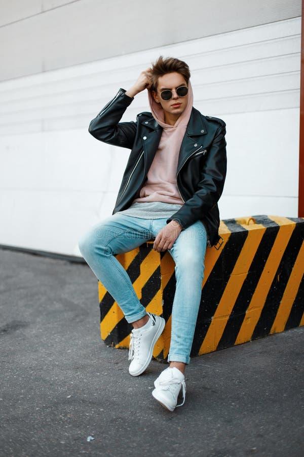 Homem novo americano à moda do moderno em uma camiseta cor-de-rosa em óculos de sol na moda em um casaco de cabedal nas calças de imagens de stock royalty free
