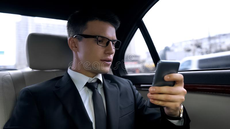 Homem novo ansioso no terno que recebe a mensagem com más notícias, passeio no automóvel luxuoso imagens de stock