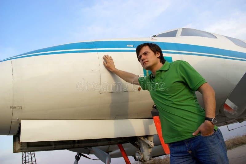 Homem novo ao lado do avião imagem de stock royalty free