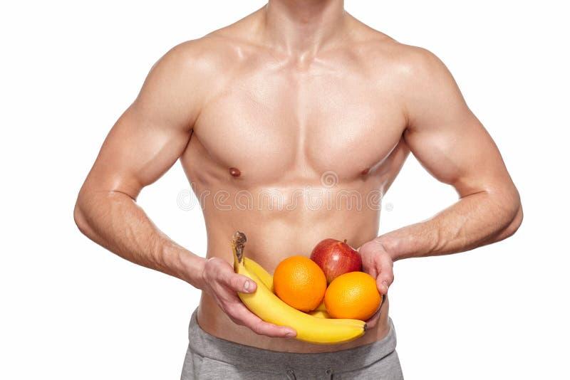 Homem novo apto com o torso bonito que guarda o fruto foto de stock royalty free