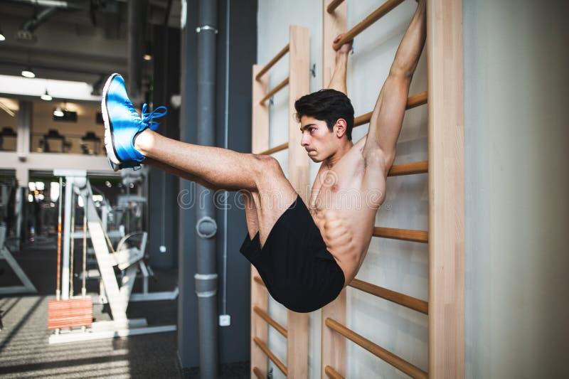 Homem novo apto no gym que dá certo em barras de parede fotos de stock royalty free
