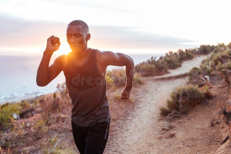 Homem novo apto que corre apenas ao longo de uma fuga do perto do oceano fotos de stock