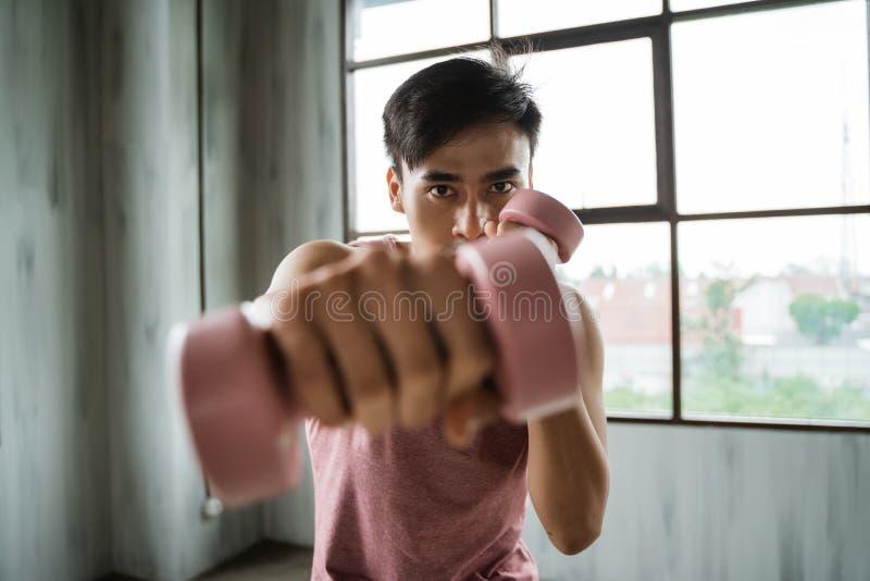 Homem novo asiático com o peso que faz o exercício do peso foto de stock