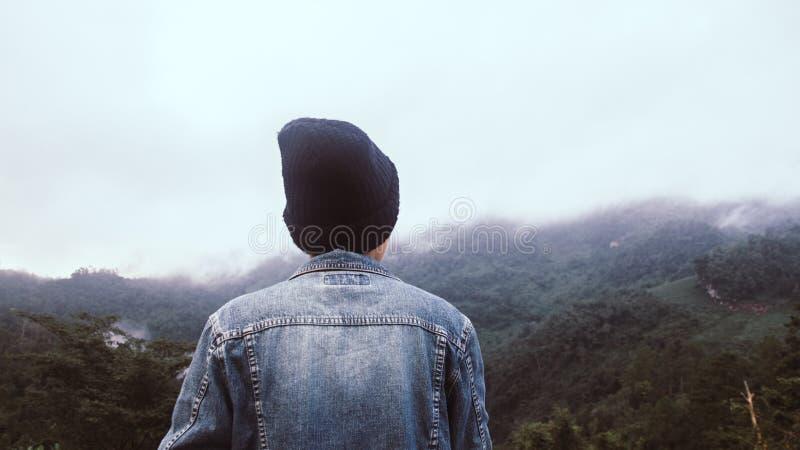 Homem novo asiático no jecket de Jean e chapéu negro que caminha no pico de montanha acima das nuvens e do caminhante da névoa ex foto de stock