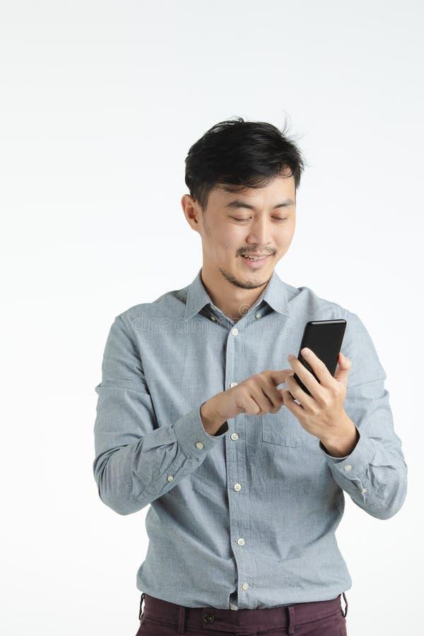 Homem novo asiático que usa o smartphone fotos de stock