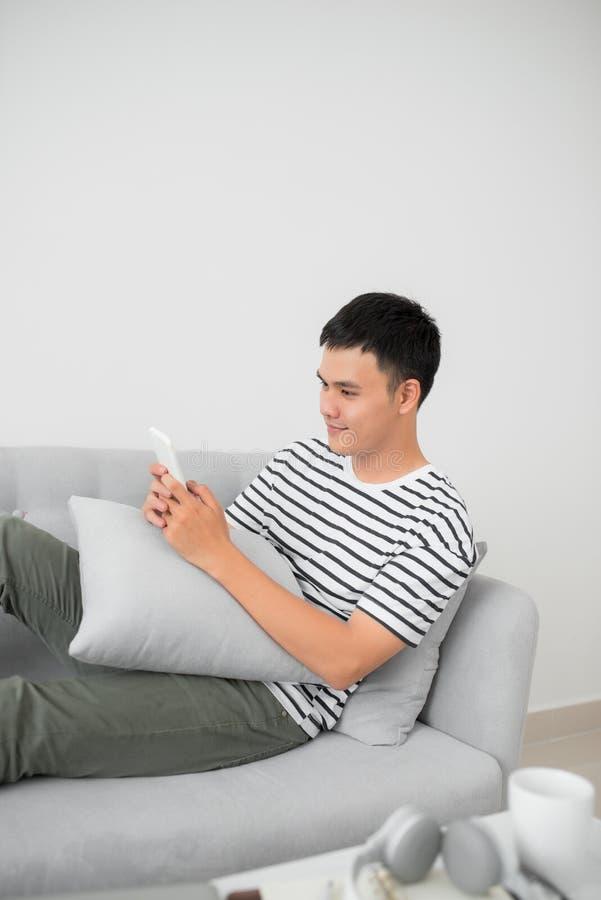 Homem novo asiático que usa o telefone celular ao encontrar-se interno foto de stock royalty free