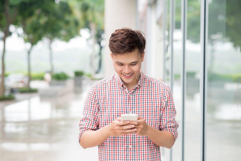 Homem novo asiático que usa o telefone esperto exterior fotografia de stock