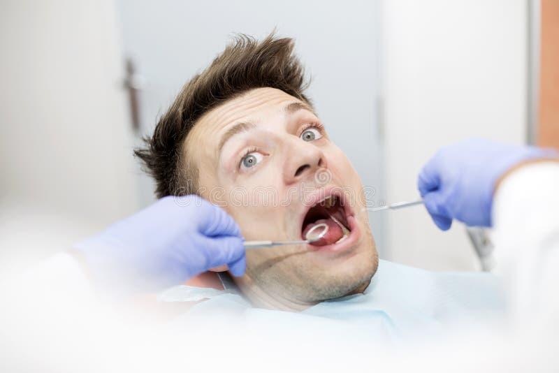 Homem novo assustado no escritório do dentista imagens de stock