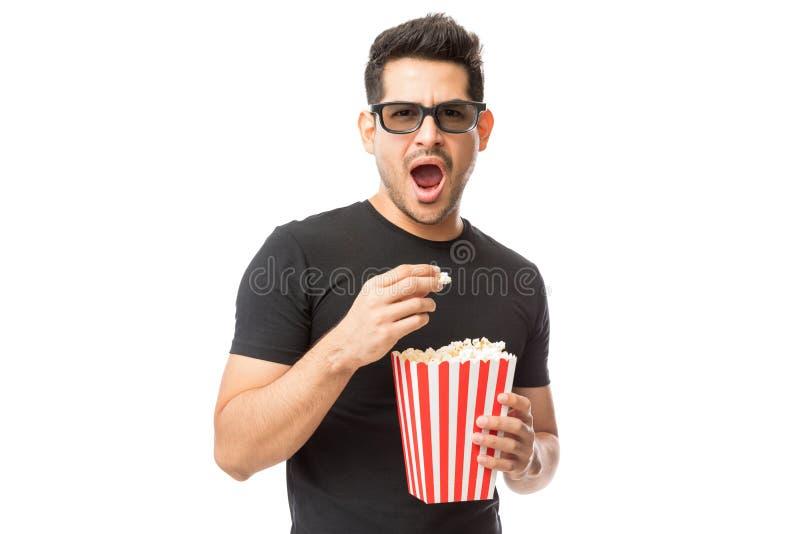 Homem novo assustado que veste os vidros 3D ao comer a pipoca imagem de stock