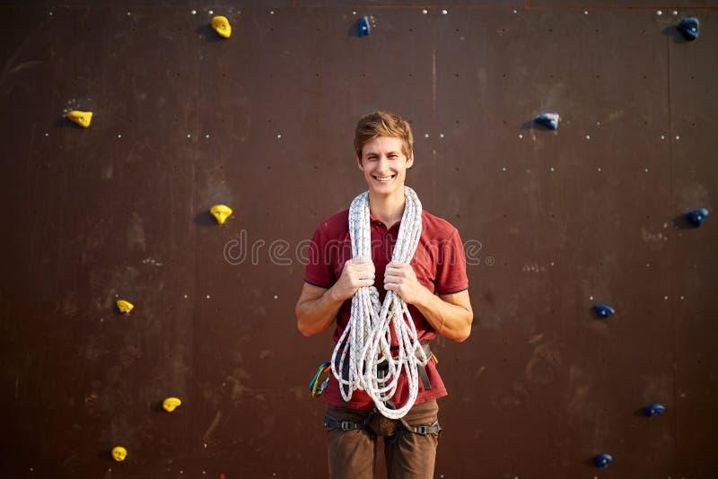 Homem novo ativo no sportswear que está com corda em ombros contra a parede de escalada do treinamento artificial Sorriso fotos de stock