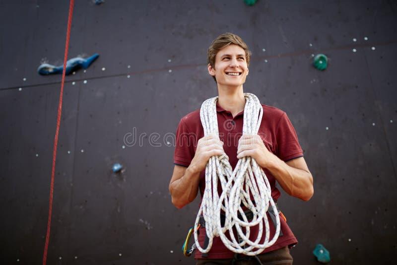 Homem novo ativo no sportswear que está com corda em ombros contra a parede de escalada do treinamento artificial Sorriso fotografia de stock royalty free