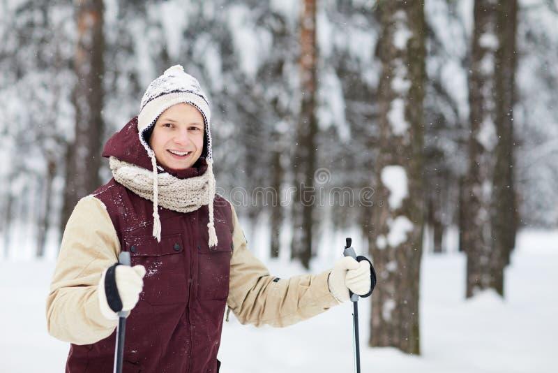 Homem novo ativo que esquia na neve foto de stock royalty free