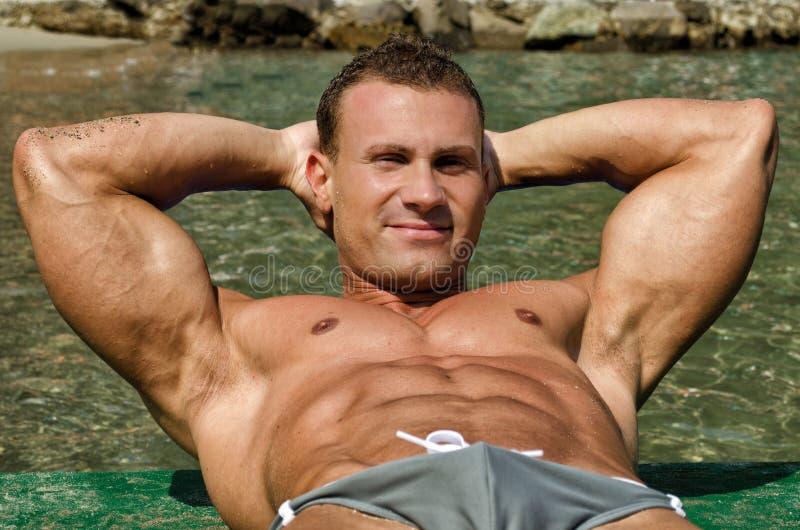 Homem novo, atlético atrativo do músculo na praia imagens de stock royalty free