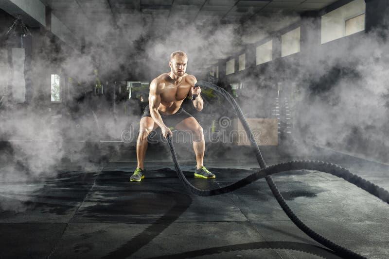 Homem novo atlético com a corda da batalha que faz o exercício no gym da aptidão fotografia de stock royalty free