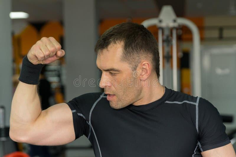 Homem novo atlético considerável que mostra seu bíceps que levanta no gym foto de stock