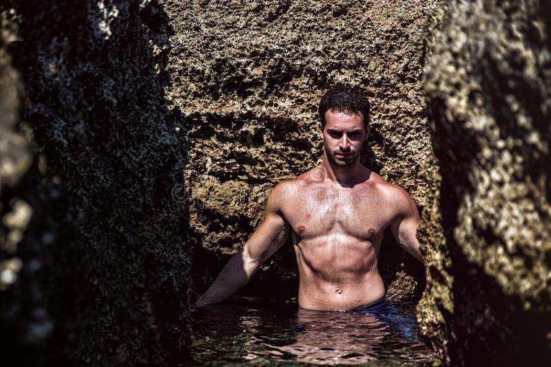 Homem novo atlético no mar ou no oceano por rochas imagens de stock