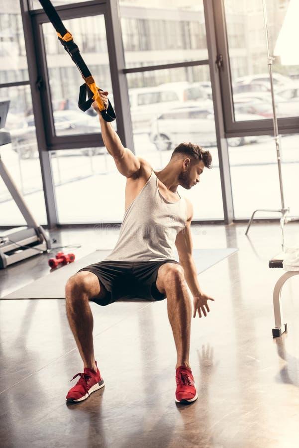 homem novo atlético no sportswear que exercita com correias da suspensão fotografia de stock