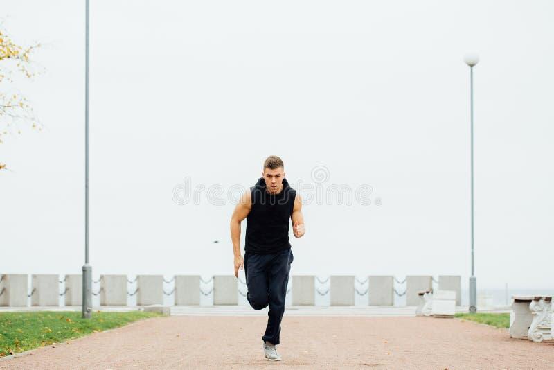 Homem novo atlético que corre na natureza Estilo de vida saudável imagens de stock royalty free