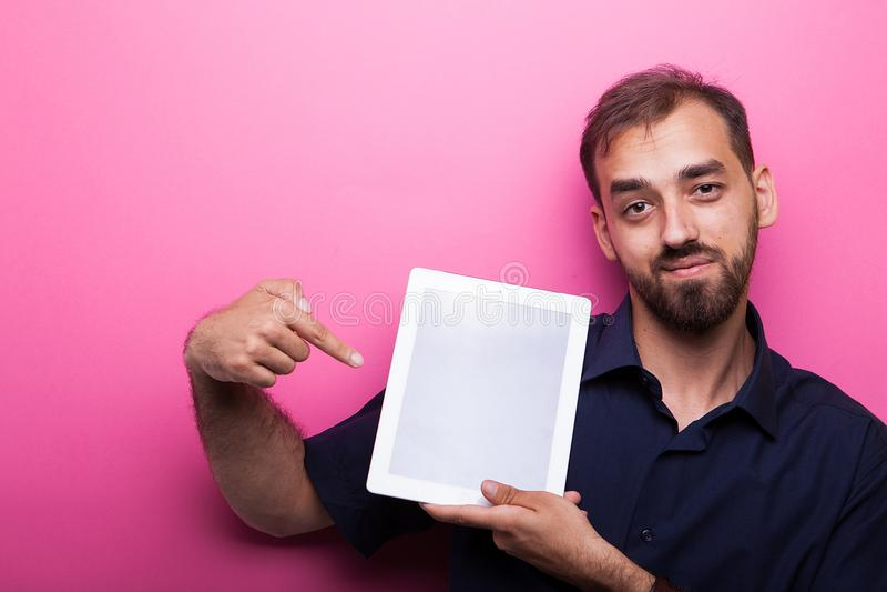 Homem novo atrativo bonito que mostra seu PC da tabuleta imagem de stock