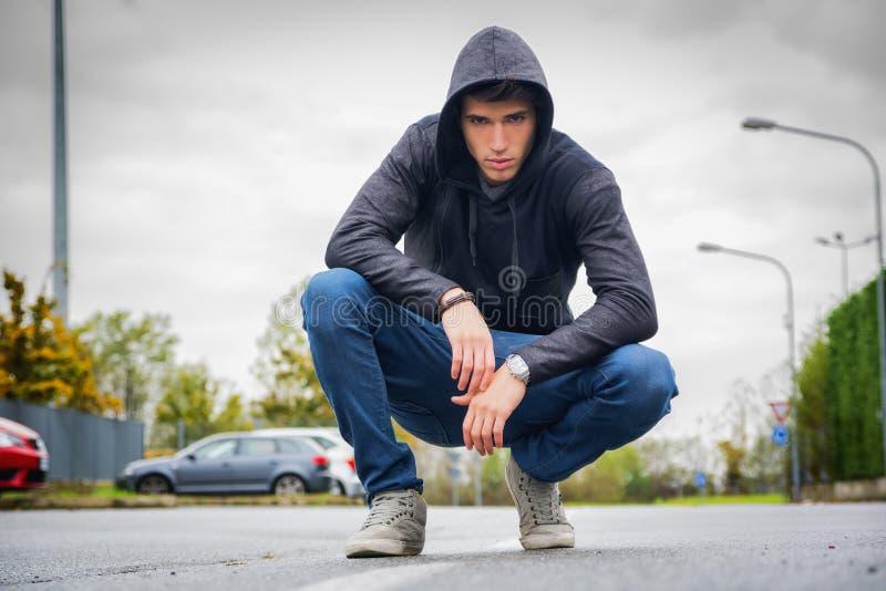 Homem novo atrativo com hoodie e boné de beisebol na rua da cidade fotos de stock royalty free
