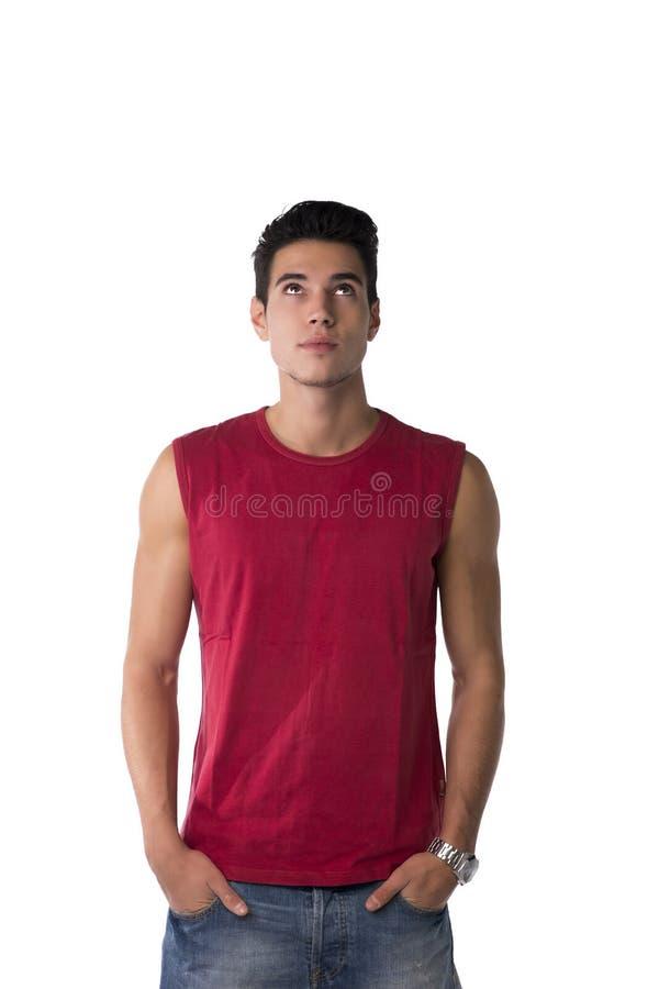 Homem novo atrativo na camisa vermelha e nas calças de brim sem mangas, olhando acima foto de stock