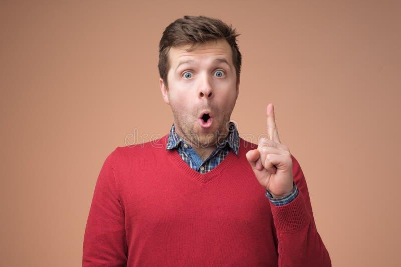 Homem novo atrativo na camiseta vermelha que aponta acima com seu dedo fotografia de stock royalty free