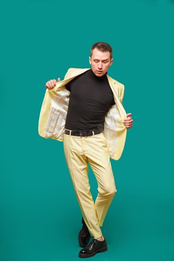 Homem novo atrativo na dança do terno, tendo o divertimento no fundo da hortelã Probabilidade à moda, homem de negócios bem suced foto de stock royalty free