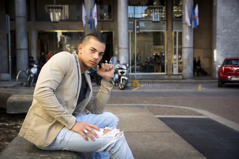 Homem novo atrativo no ajuste urbano, assento foto de stock royalty free
