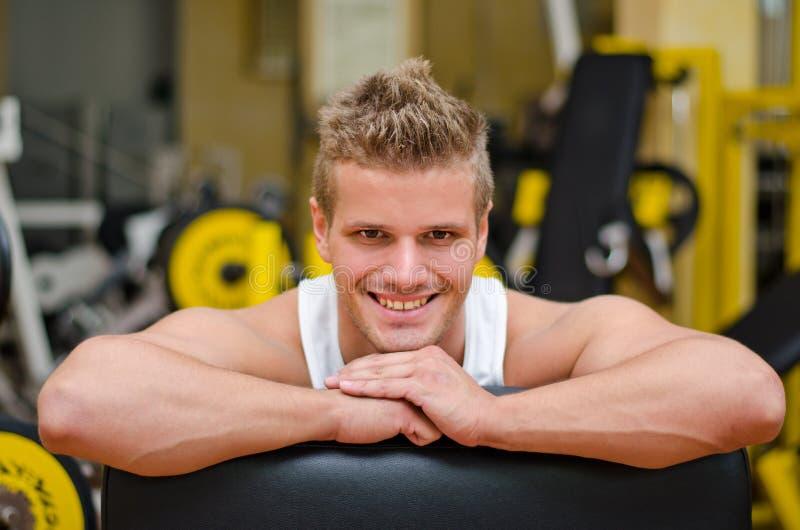 Homem novo atrativo no gym que descansa no equipamento do gym imagens de stock royalty free