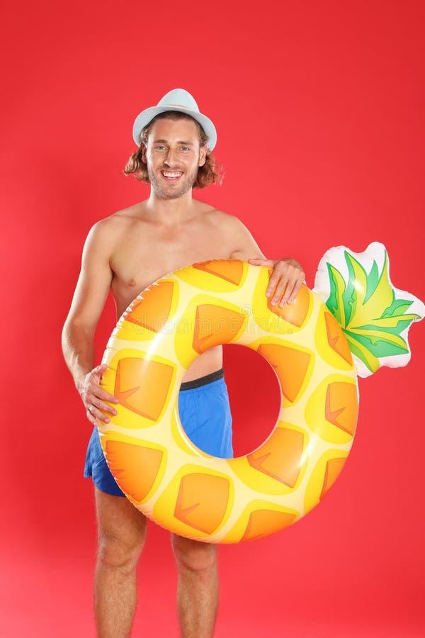 Homem novo atrativo no roupa de banho com anel inflável do abacaxi imagens de stock royalty free