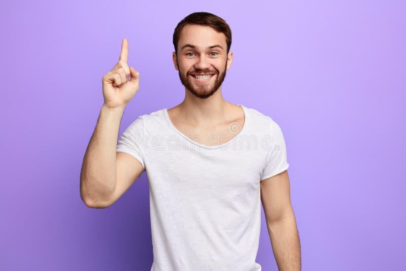 Homem novo atrativo no t-shirt do whilte que aponta acima de seu dedo foto de stock