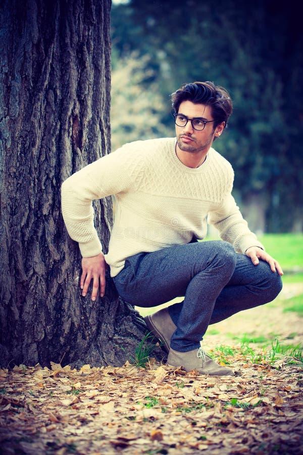 Homem novo atrativo perto de uma árvore em um parque imagem de stock royalty free