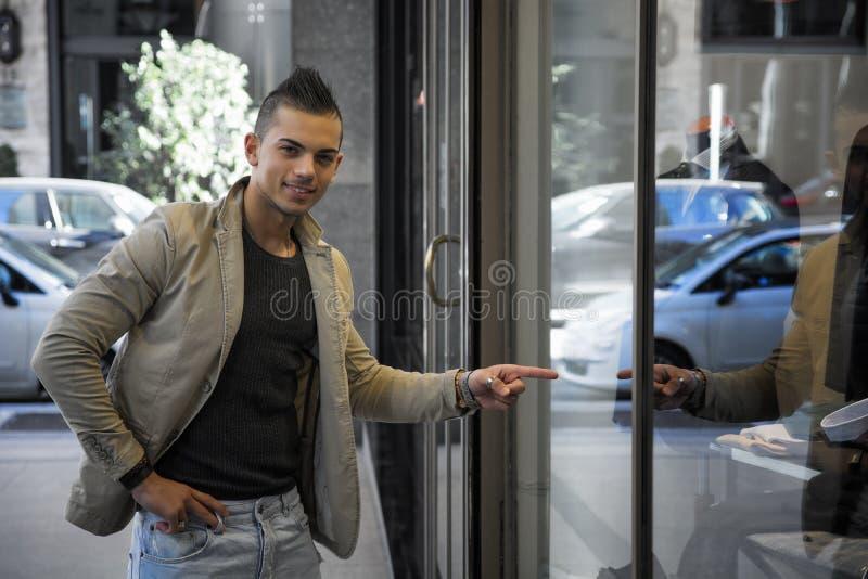Homem novo atrativo que aponta o dedo na janela da loja imagem de stock royalty free