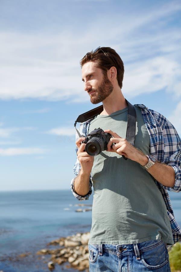 Homem novo, atrativo que está perto do oceano com camer digital fotos de stock