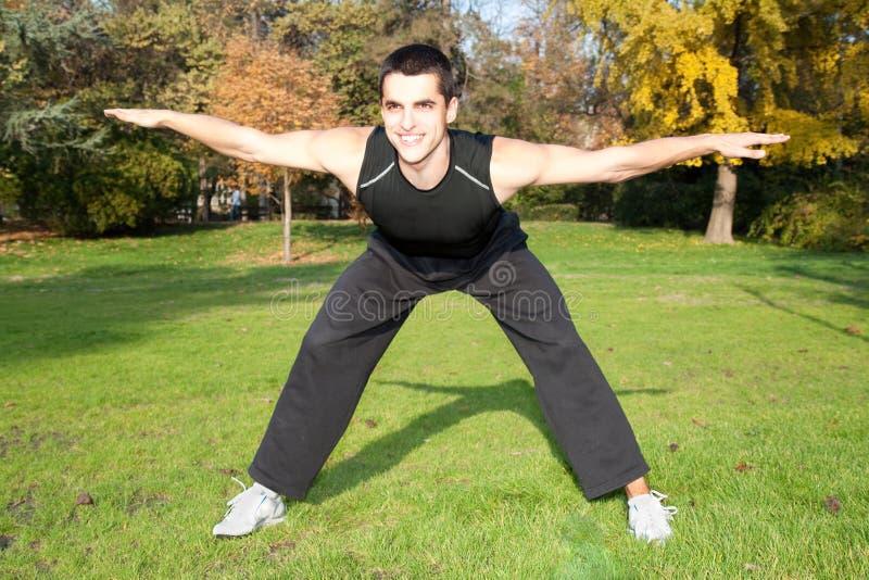Homem novo atrativo que faz o exercício no parque imagem de stock