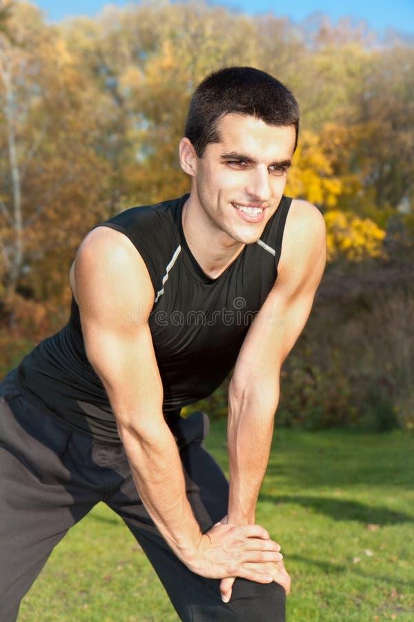 Homem novo atrativo que faz o exercício no parque fotos de stock royalty free