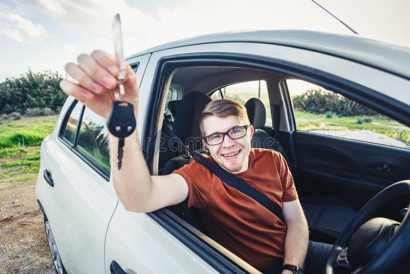 Homem novo atrativo que mostra seus chaves e sorriso novos do carro foto de stock