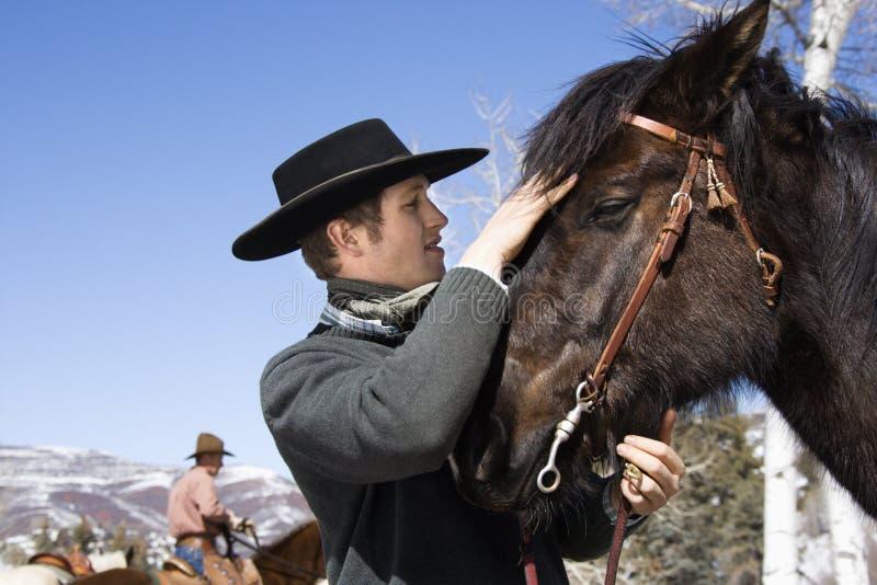 Homem novo atrativo que Petting o cavalo fotos de stock royalty free