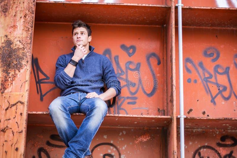 Homem novo atrativo que senta-se na estrutura alaranjada do metal imagem de stock royalty free