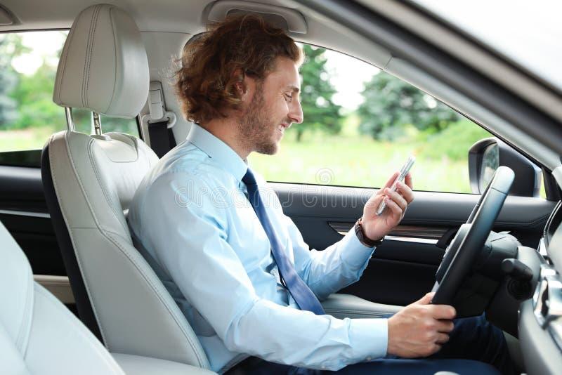 Homem novo atrativo que usa o telefone ao conduzir seu carro foto de stock