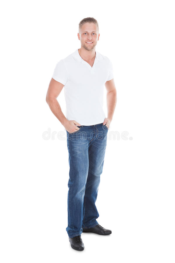 Homem novo atrativo 'sexy' relaxado nas calças de brim e em um t-shirt branco imagem de stock
