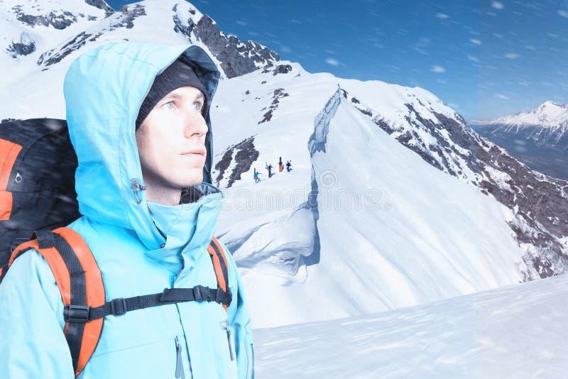 Homem novo aventuroso com a trouxa que est? na opini?o superior da montanha e que olha para fora Passeio dos Snowboarders subida  imagens de stock royalty free