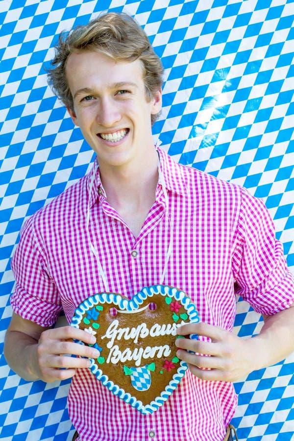 Homem novo bávaro que guarda um pão-de-espécie coração-dado forma foto de stock