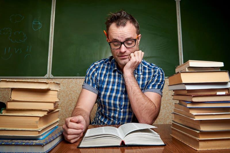 Homem novo bagunçado nos vidros que lê um livro na tabela com as pilhas dos livros no fundo do quadro-negro imagens de stock royalty free