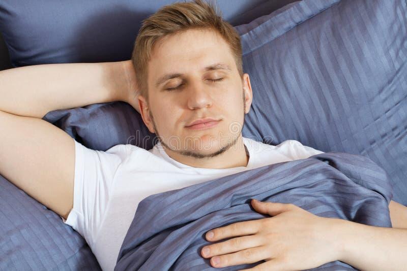 Homem novo bonito do retrato que dorme no quarto da cama fotos de stock