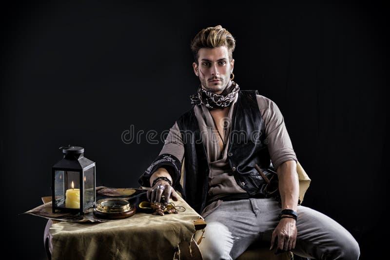 Homem novo bonito no equipamento da forma do pirata que senta-se ao lado da tabela fotografia de stock royalty free