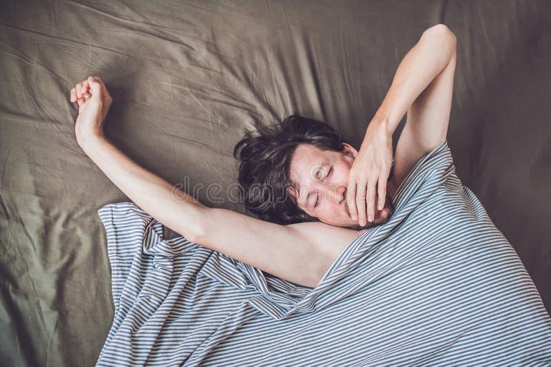 Homem novo bonito que encontra-se para baixo na cama e que dorme, vista superior Não obtenha bastante conceito do sono fotografia de stock