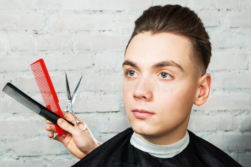 Homem novo branco com penteado do Pompadour no barbeiro em um fundo da parede de tijolo com pentes e tesouras foto de stock