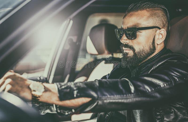 Homem novo brutal considerável atrás da roda de um carro luxuoso imagem de stock